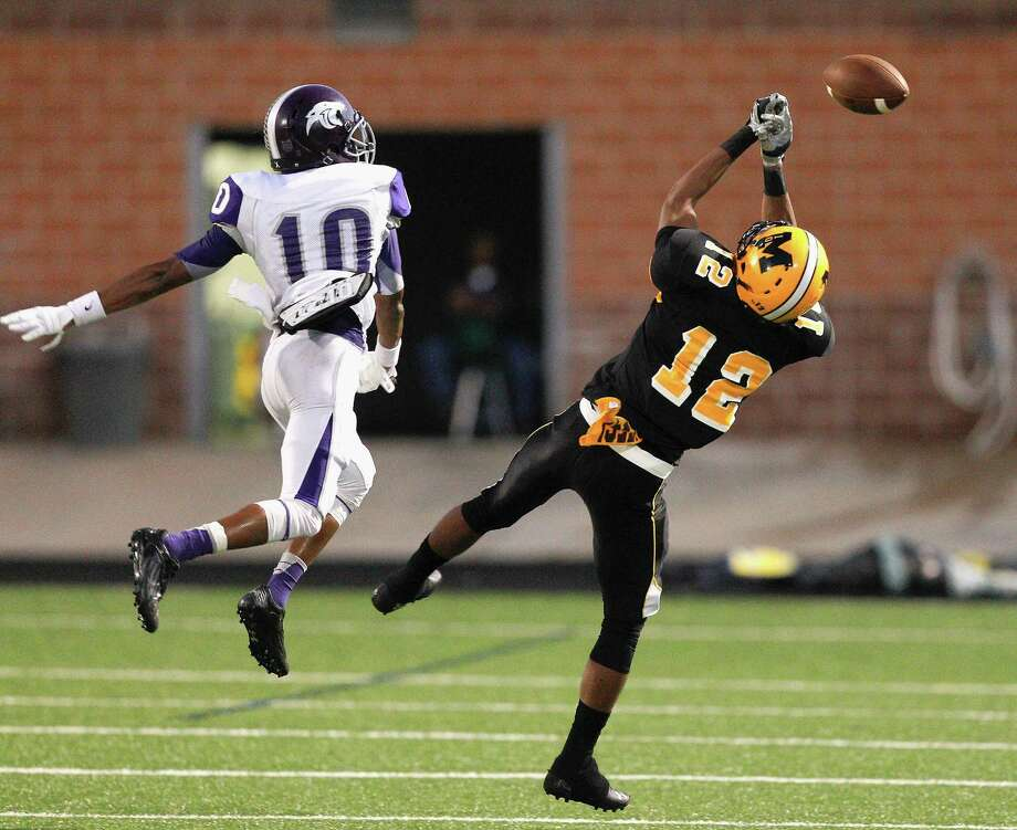 Fort Bend Marshall's Jeremey Smith (12) has the ball slips through his hands as he is defended by Ridge-Point's Jordan Tolbert during a high school football game between Ridge Point and Fort Bend Marshall Friday October 4, 2013. (Bob Levey/For The Chronicle) Photo: Bob Levey, Houston Chronicle / ©2013 Bob Levey