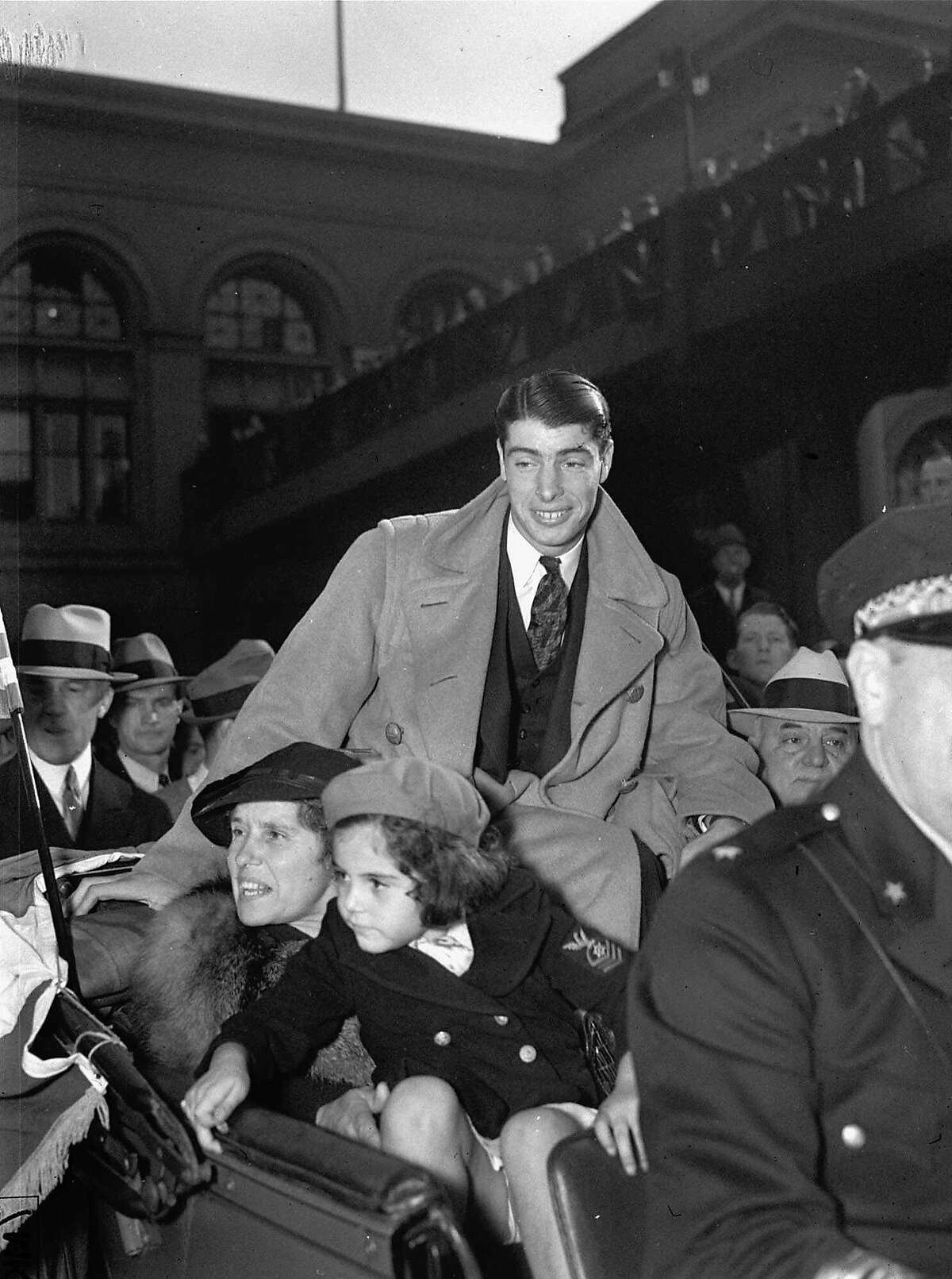 A rousing welcome was accorded Joe DiMaggio, New York Yankee outfielder and San Francisco's baseball idol, when he returned home in this Oct. 13, 1936 photo after taking part in the World Series in his first year in the majors. The sensational rookie is shown riding up Market Street in the Mayor's car with his mother and a niece. DiMaggio, the elegant Yankee Clipper whose 56-game hitting streak endures as one of the most remarkable records in baseball or any sport, died Monday, March 8, 1999 at his home in Hollywood, Fla. He was 84. (AP Photo/FILE0