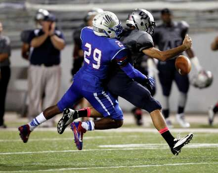 College Park's Philip Achee, right, fumbles the ball after being tackled by Oak Ridge's Llewelldyn Jones during the first half of a high school football game, Friday, October 4, 2013 at Woodforest Stadium in Shenandoah. Photo: Eric Christian Smith, For The Chronicle