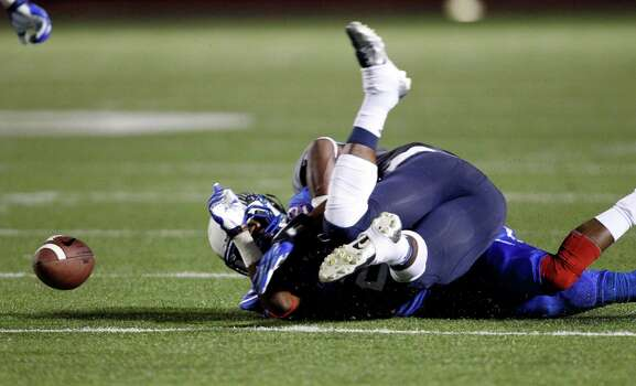 Oak Ridge's Lamar Handy, right, fumbles the ball after being tackled by College Park's Eric Harrell during the first half of a high school football game, Friday, October 4, 2013 at Woodforest Stadium in Shenandoah. Photo: Eric Christian Smith, For The Chronicle