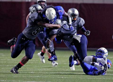 Oak Ridge's Jamarqus Durst (3) is tackled by College Park's Tristan Newman, left, and Eric Harrell during the first half of a high school football game, Friday, October 4, 2013 at Woodforest Stadium in Shenandoah. Photo: Eric Christian Smith, For The Chronicle