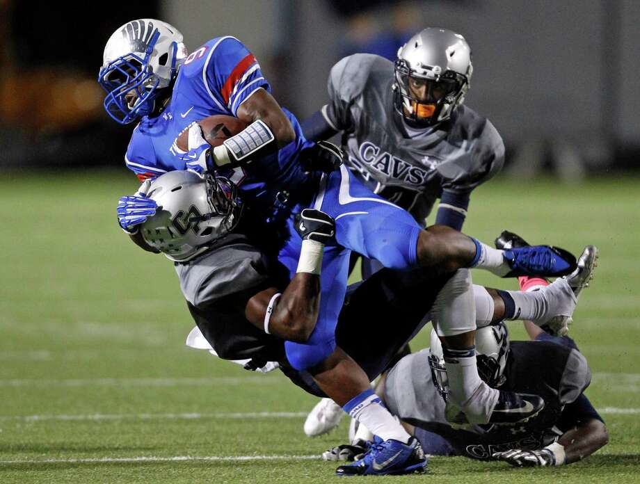 Oak Ridge's Kwame Etwi, top, is tackled by College Park's Eric Harrell during the first half of a high school football game, Friday, October 4, 2013 at Woodforest Stadium in Shenandoah. Photo: Eric Christian Smith, For The Chronicle