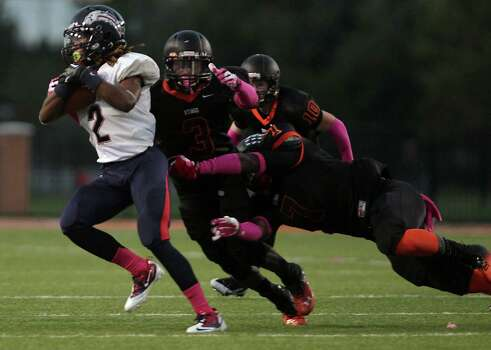 Dawson's Brett Winnegan left, is tackled by Texas City's Armanti Foreman 2nd from left, during the first quarter of high school football game action at Texas City ISD's Stingaree Stadium Friday, Oct. 4, 2013, in Texas City. Photo: James Nielsen, Houston Chronicle / © 2013  Houston Chronicle