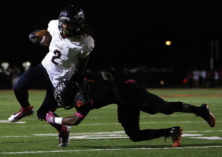 Dawson's Brett Winnegan left, is tackled by Texas City's  Donald Lynch during the second quarter of high school football game action at Texas City ISD's Stingaree Stadium Friday, Oct. 4, 2013, in Texas City. Photo: James Nielsen, Houston Chronicle / © 2013  Houston Chronicle