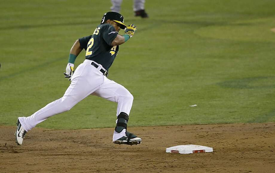 Yoenis Céspedes rounds second base on his way to a second-inning triple - the A's first hit. Photo: Jeff Chiu, Associated Press