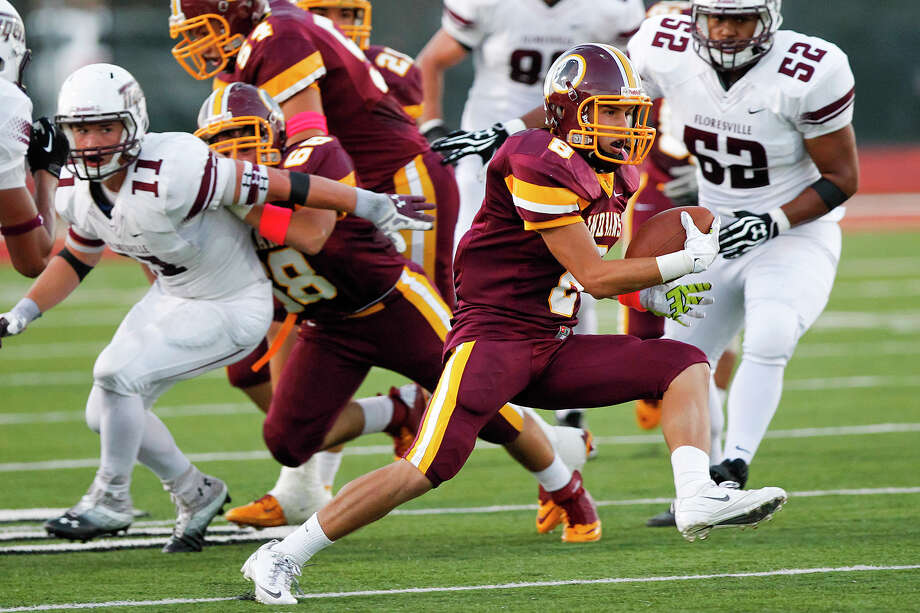 Harlandale's Eddie Pedroza (second from right) picks up yardage during the first half of their game at Harlandale Memorial Stadium on Oct. 4, 2013.  Harlandale beat the Tigers 28-17. Photo: Marvin Pfeiffer, San Antonio Express-News / Express-News 2013