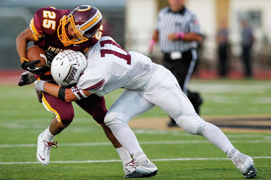 Floresville's Kyle Pippert (right) tackles Harlandale's John Aguirre during the first half of their game at Harlandale Memorial Stadium on Oct. 4, 2013.  Harlandale beat the Tigers 28-17. Photo: Marvin Pfeiffer, San Antonio Express-News / Express-News 2013