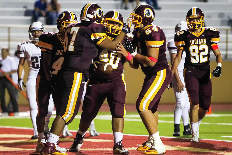 Harlandale's Juan Moncivaiz (center) is congratulated by Zachary Borrego (right) and Edmundo Maldonado after his fourth quarter touchdown reception during their game with at Floresville at Harlandale Memorial Stadium on Oct. 4, 2013. Harlandale beat the Tigers 28-17. Photo: Marvin Pfeiffer, San Antonio Express-News / Express-News 2013