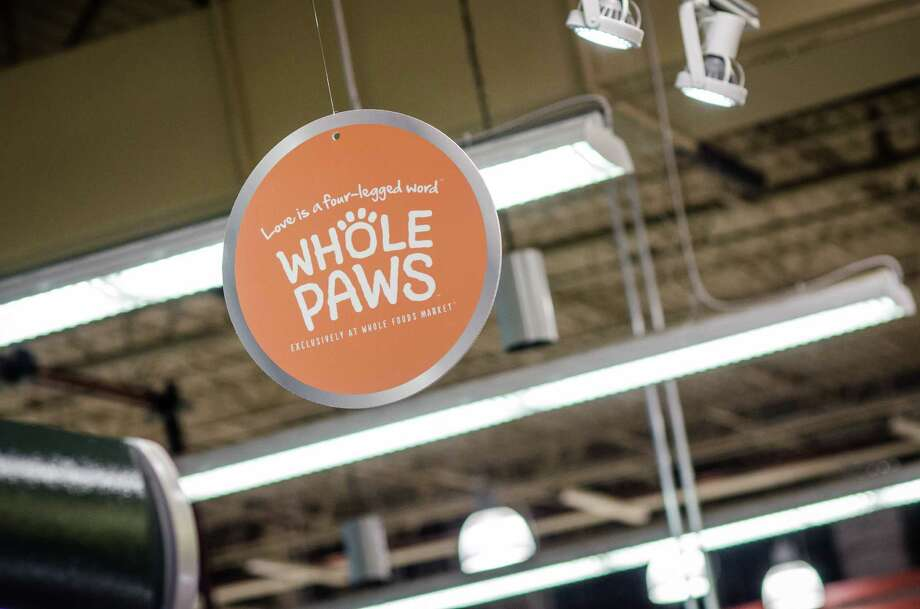 A dog owner looks at the ingredients of Whole Foods' new pet food line. Whole Paws is a premium line, but a Whole Foods official says the dry and wet foods will cost less than other premium brands the chain sells. Photo: Jamaal Ellis / ©2013 Houston Chronicle