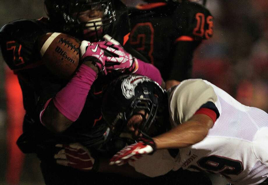 Texas City's D'Onta Foreman left, is hit by Dawson's Brandon Guzman while scoring a touchdown during the second quarter of high school football game action at Texas City ISD's Stingaree Stadium Friday, Oct. 4, 2013, in Texas City. Photo: James Nielsen, Houston Chronicle / © 2013  Houston Chronicle