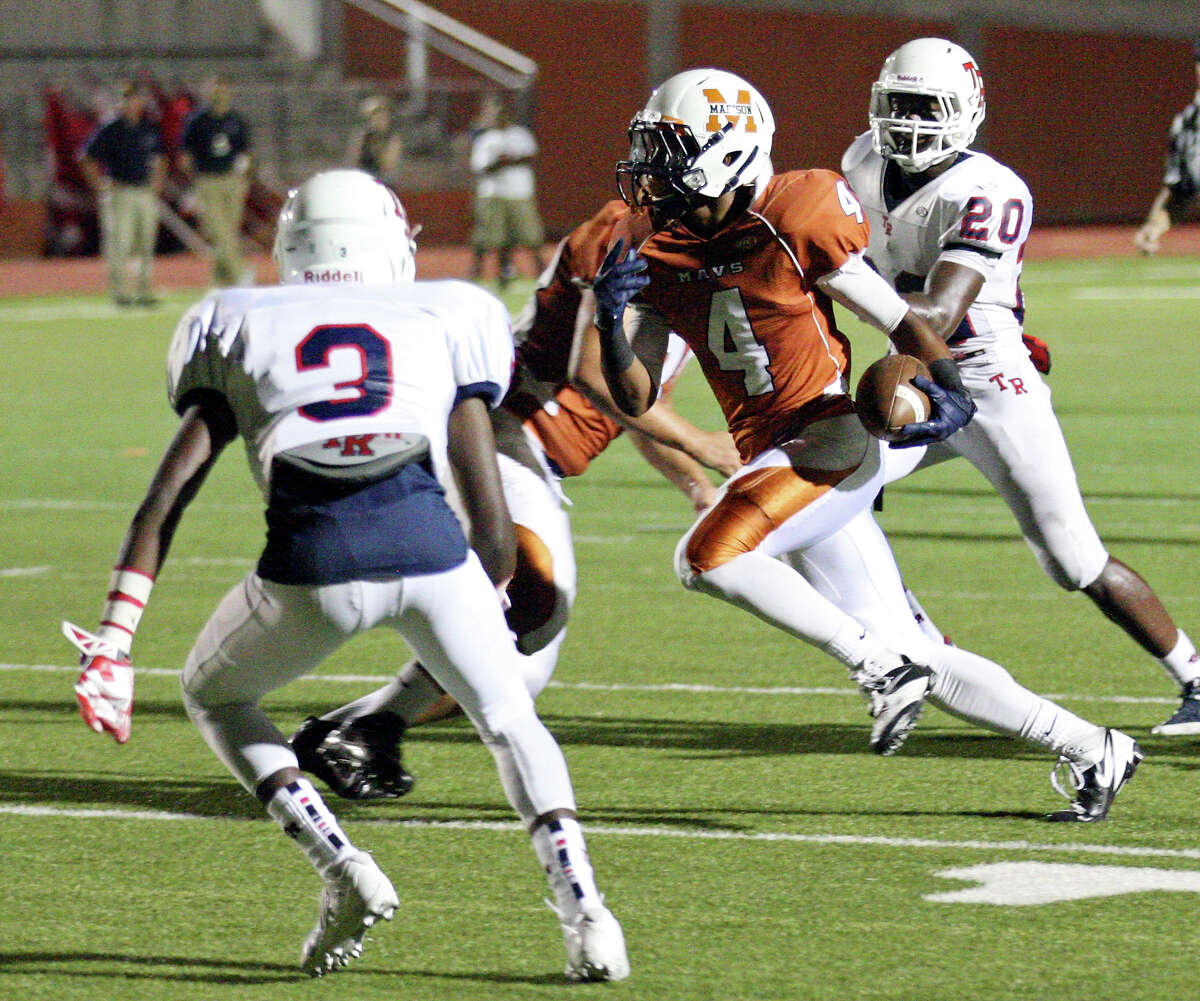 Madison's Byron Daniels head to the end zone for a touchdown between Roosevelt's Khalid Mitchell (left) and Victor Hunter during first half action Friday Oct. 4, 2013 at Heroes Stadium.
