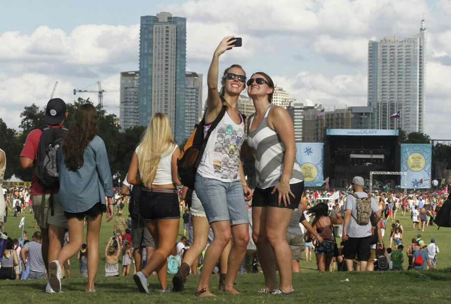 Rikki Risinger (left) and Chelsea Moody photograph themselves on the opening day of the Austin City Limits Music Festival at Zilker Park. Opening weekend is sold out. But tickets are available for Weekend 2 of festival next weekend. No longer are single-day wristbands being sold. Three-day passes cost $225, and more expensive VIP packages are available. Photo: Jack Plunkett / Invision / Associated Press