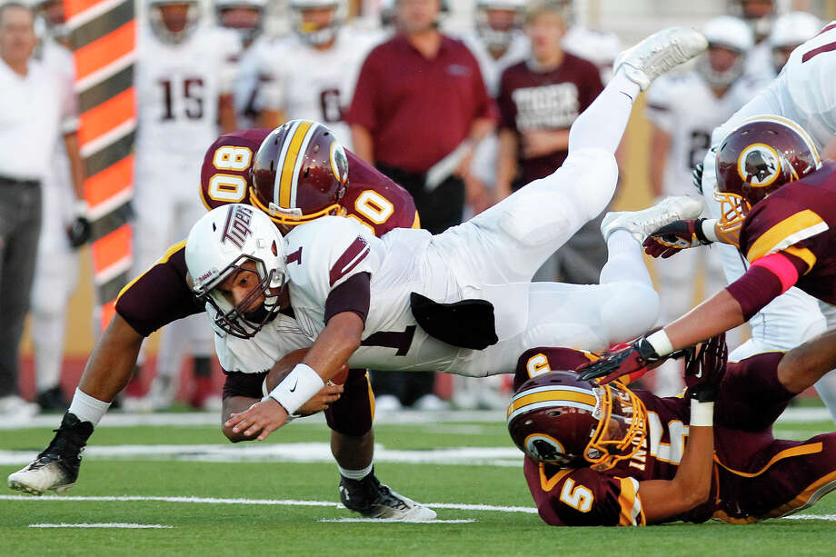 Floresville running back Gilbert Ortiz (1) dives over Harlandale's Ruben Zavala as he's hit from behing by Raymond Medina during the first quarter of their game at Harlandale Memorial Stadium on Oct. 4, 2013. Photo: Marvin Pfeiffer, San Antonio Express-News / Express-News 2013