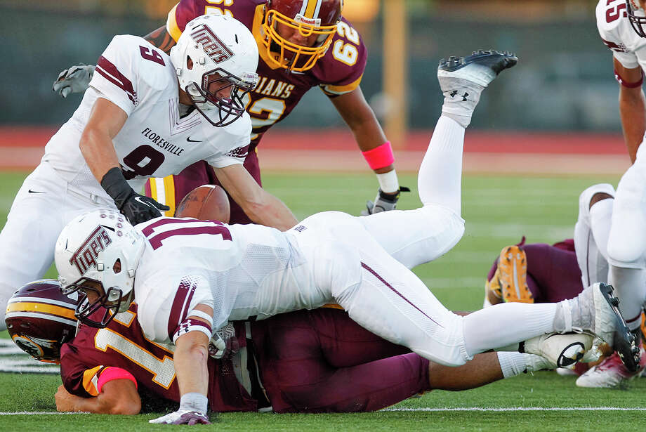 Harlandale quarterback Brandon Ramon (lower left) loses the ball on a first quarter run during their game with Floresville at Harlandale Memorial Stadium on Oct. 4, 2013. Photo: Marvin Pfeiffer, San Antonio Express-News / Express-News 2013