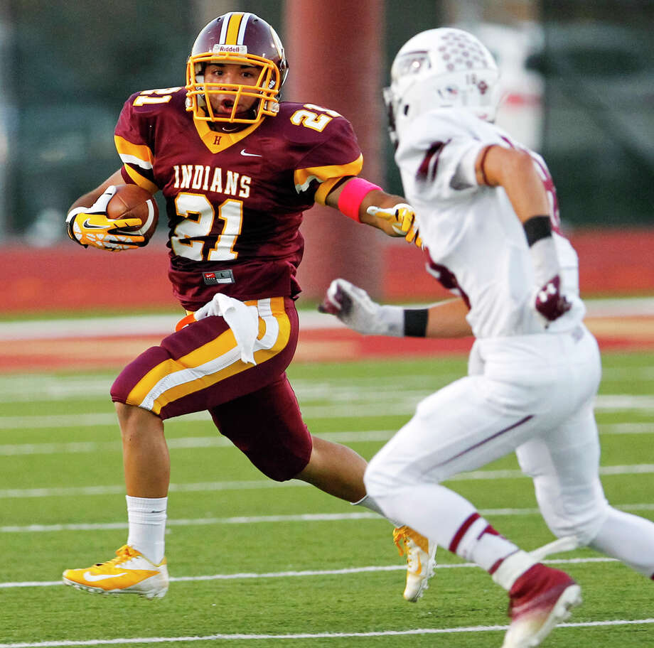 Harlandale running back Nicholas Martinez (left) tries to run past Floresville's Bradley Bunn during the first half of their game at Harlandale Memorial Stadium on Oct. 4, 2013. Photo: MARVIN PFEIFFER, Marvin Pfeiffer/ Express-News / Express-News 2013