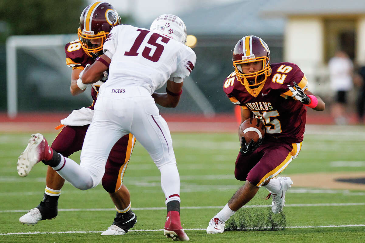 Harlandale's James Medoza (left) blocks Floresville's Vernon Marsh to clear the way for John Aguirre (right) during the first half of their game at Harlandale Memorial Stadium on Oct. 4, 2013.