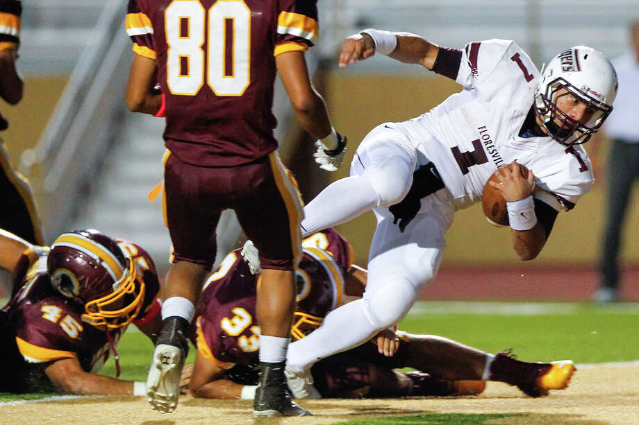 Floresville running back Gilbert Ortiz (right) scores a four-yard touchdown during the second quarter of their game with Harlandale at Harlandale Memorial Stadium on Oct. 4, 2013.  Ortiz was injured on the4 play and did not return to the game. Photo: Marvin Pfeiffer, San Antonio Express-News / Express-News 2013