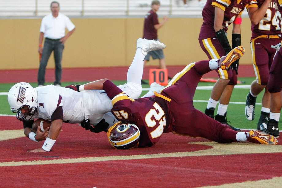 Floresville running bafck Gilbert Ortiz (left) dives into the end zone for a first quarter touchdown despite the efforts of Harlandale's Damien Avina during their game at Harlandale Memorial Stadium on Oct. 4, 2013. Photo: Marvin Pfeiffer, San Antonio Express-News / Express-News 2013
