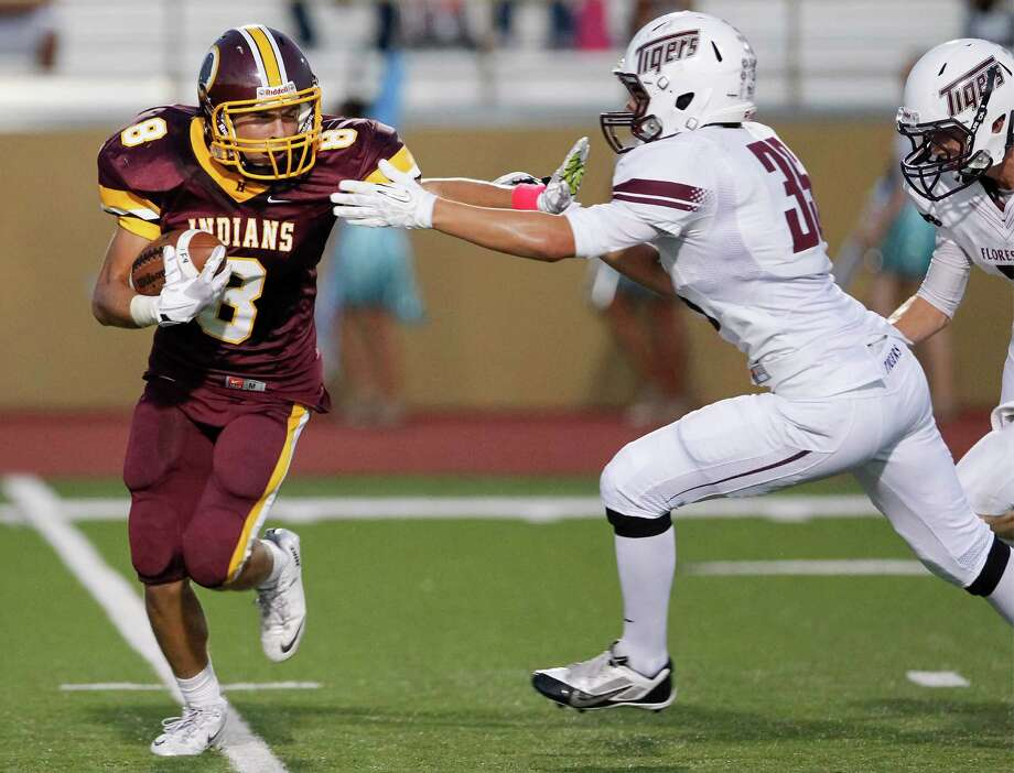 Harlandale's Eddie Pedroza (left) tries to elude Floresville's Zach Frantz during the first half of their game at Harlandale Memorial Stadium on Oct. 4, 2013.  Harlandale beat the Tigers 28-17. Photo: Marvin Pfeiffer, San Antonio Express-News / Express-News 2013