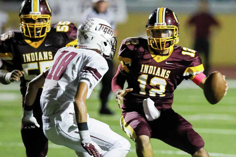 Harlandale quarter back Brandon Ramon (right) fakes a pitch to his left on Floresville's Bradley Bunn  before scoring a second quarter touchdown during their game at Harlandale Memorial Stadium on Oct. 4, 2013. Photo: MARVIN PFEIFFER, Marvin Pfeiffer/ Express-News / Express-News 2013