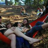 From left, Khala Brannigan, 20, Rasta Moja, 21, Katya Bitar, 22, and Jay Zus, 21, hang out in a hammock together up the hill from one of the stages and enjoy live music during the first day of the Hardly Strictly Bluegrass festival in Golden Gate Park October 4, 2013 in San Francisco, Calif.