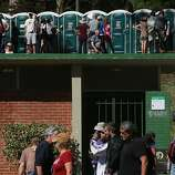 Festival goers are seen waiting for bathrooms while others walk through Hellman Hollow at the Hardly Strictly Bluegrass Festival in Golden Gate Park, in San Francisco, Ca, on Friday, Oct. 4, 2013.