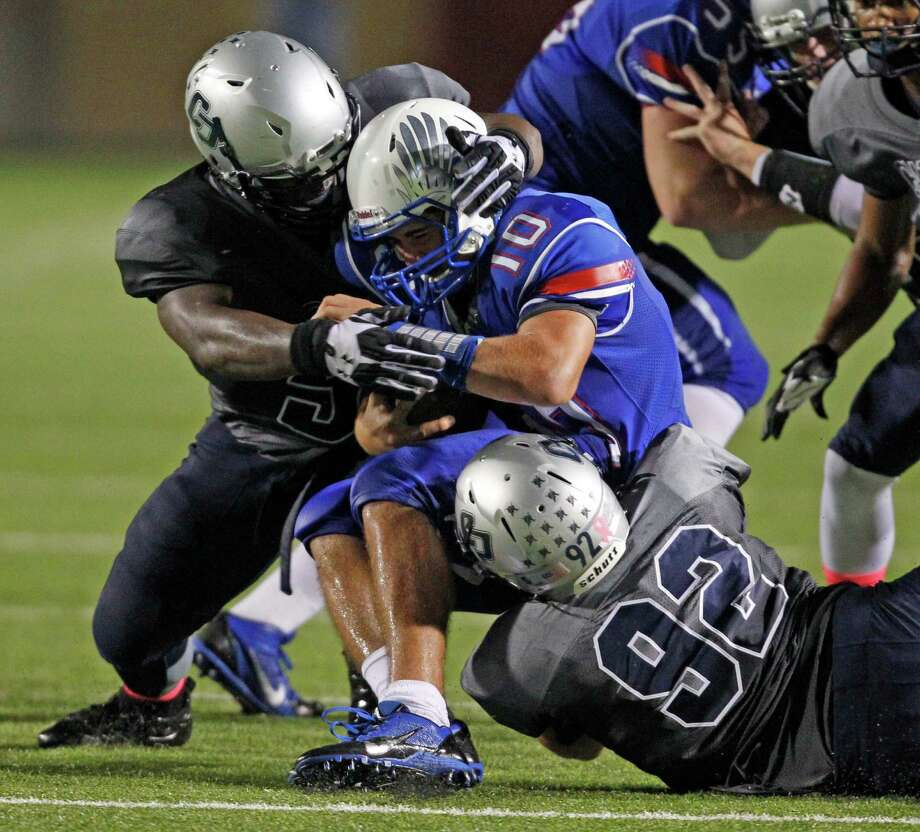 Oak Ridge's Braden Letney (10) is tackled by College Park's Jayvon Jackson, left, and Luis Espinola (92) during the second half of a high school football game, Friday, October 4, 2013 at Woodforest Stadium in Shenandoah. Photo: Eric Christian Smith, For The Chronicle