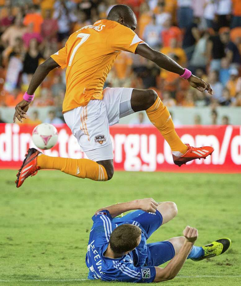 Houston Dynamo forward Omar Cummings leaps over Montreal Impact midfielder Wandrille Lefevre during the second half of an MLS soccer match on Friday, Oct. 4, 2013, at BBVA Compass Stadium in Houston. Photo: Smiley N. Pool, Houston Chronicle / © 2013  Houston Chronicle