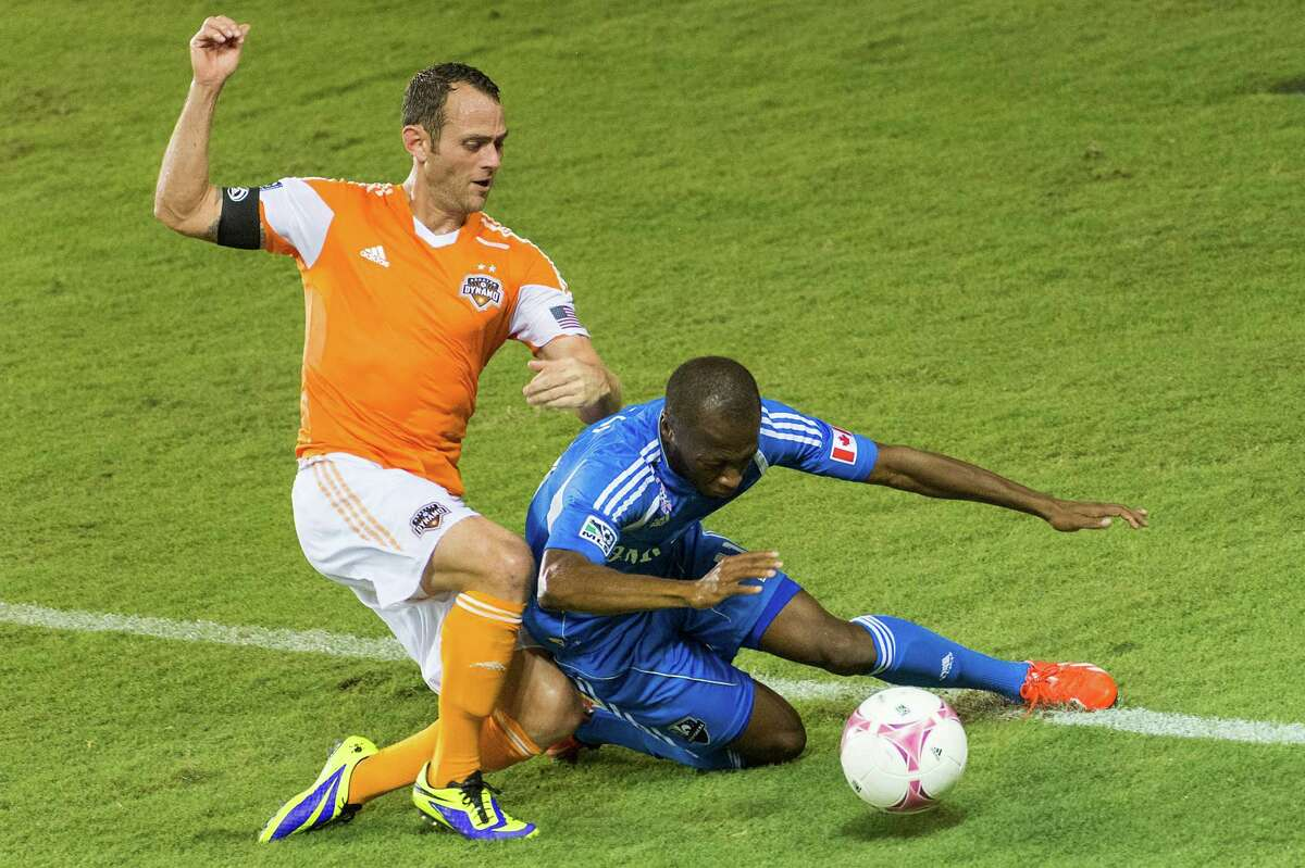 Houston Dynamo midfielder Brad Davis, left, collides with Montreal Impact midfielder Sanna Nyassi during the second half of an MLS soccer match on Friday, Oct. 4, 2013, at BBVA Compass Stadium in Houston.