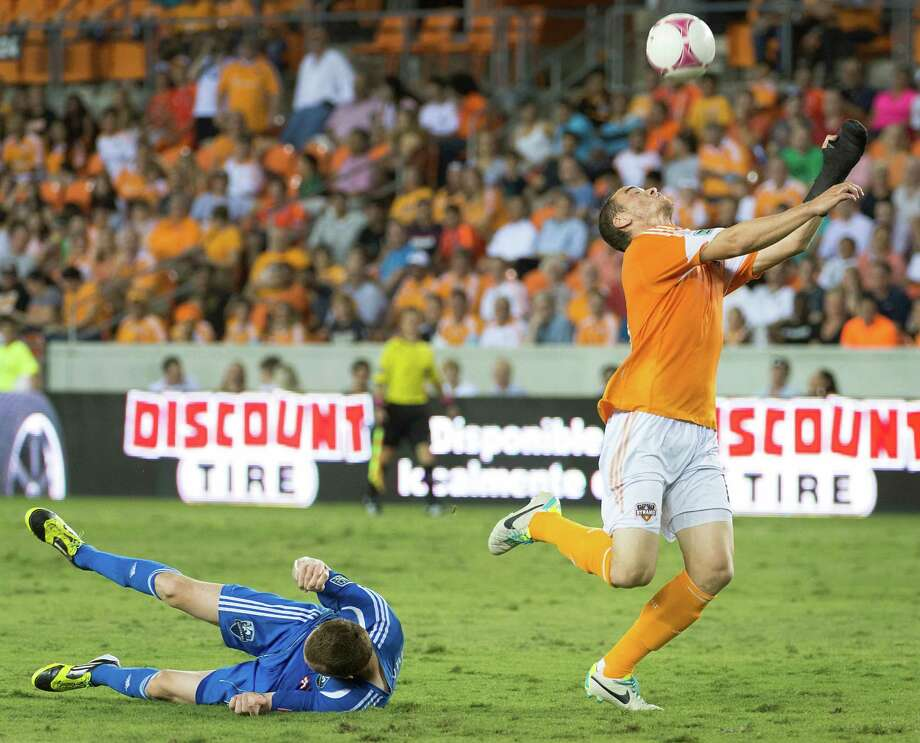 Houston Dynamo forward Cam Weaver goes for a header after getting past Montreal Impact midfielder Wandrille Lefevre during the second half of an MLS soccer match on Friday, Oct. 4, 2013, at BBVA Compass Stadium in Houston. Photo: Smiley N. Pool, Houston Chronicle / © 2013  Houston Chronicle