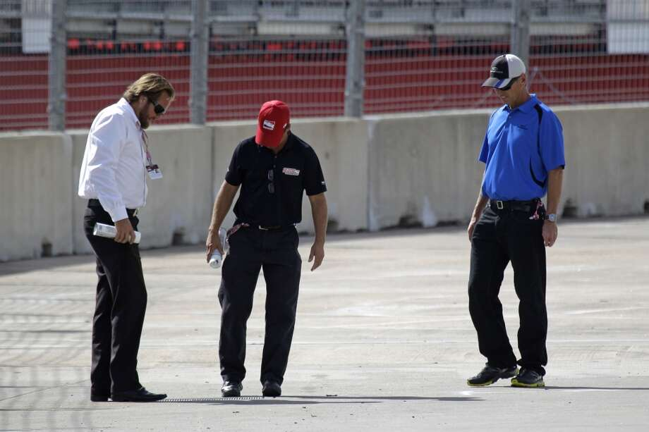 IndyCar race director Beaux Barfield, left, and other officials look at the track surface at turn one of the Grand Prix of Houston course at Reliant Park Friday, Oct. 4, 2013, in Houston.  Race practice was delayed while officials installed a temporary chicane to help driver avoid a problem with the surface of the track. IndyCar qualifying was reschedule for Saturday. Officials plan to make repairs to track overnight. ( Melissa Phillip / Houston Chronicle ) Photo: Houston Chronicle