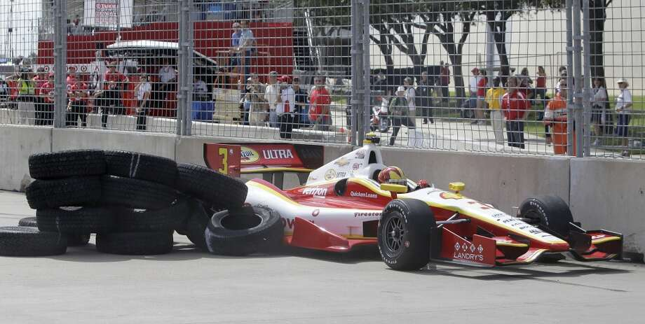 IndyCar driver, Helio Castroneves, maneuvers to avoid tires that broke loose from a temporary chicane at turn one after it was hit by Josef Newgarden in crash during practice at Grand Prix of Houston course at Reliant Park Friday, Oct. 4, 2013, in Houston. Earlier race practice was delayed while officials installed a temporary chicane to help driver avoid a problem with the surface of the track. IndyCar qualifying was reschedule for Saturday. Officials plan to make repairs to track overnight. ( Melissa Phillip / Houston Chronicle ) Photo: Houston Chronicle