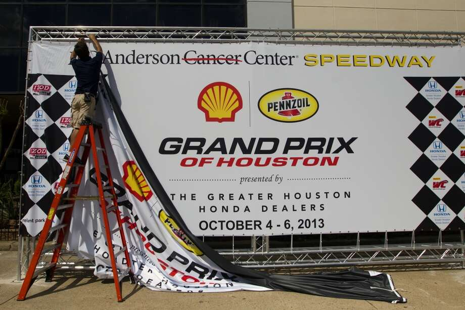 Colby Geneau hangs up a banner at the Grand Prix Houston, Friday, Oct. 4, 2013, in Houston. (Cody Duty / Houston Chronicle) Photo: Houston Chronicle