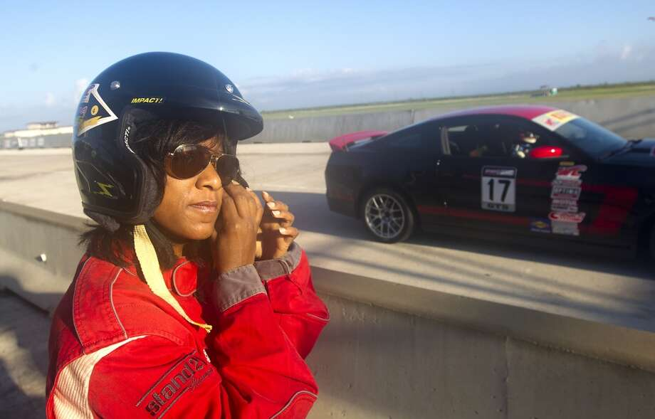 Houston Chronicle reporter Joy Sewing, left, puts on her helmet before getting into a Ford Mustang Boss 302 driven by Pirelli World Challenge driver Alec Udell at the MSR Houston Raceway, Thursday, Oct. 3, 2013, in Angleton. Udell will race in the Shell and Pennzoil Grand Prix of Houston, which starts Friday. (Cody Duty / Houston Chronicle) Photo: Houston Chronicle