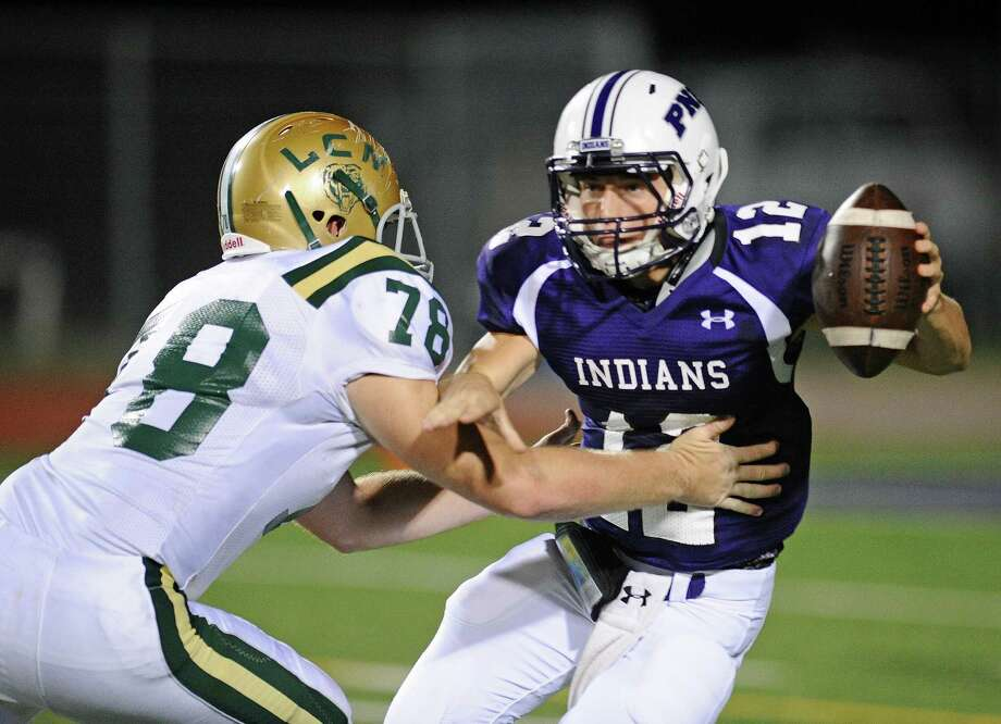 Port Neches-Groves Ky Walker (12) tries to elude Little Cypress-Mauriceville's Slade Ferguson during the second quarter of Friday's game at the Reservation.