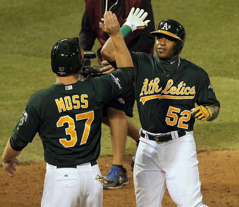 Yoenis Céspedes celebrates with Brandon Moss after the two-run homer that provided the A's only runs in Game 1. Photo: Carlos Avila Gonzalez, The Chronicle