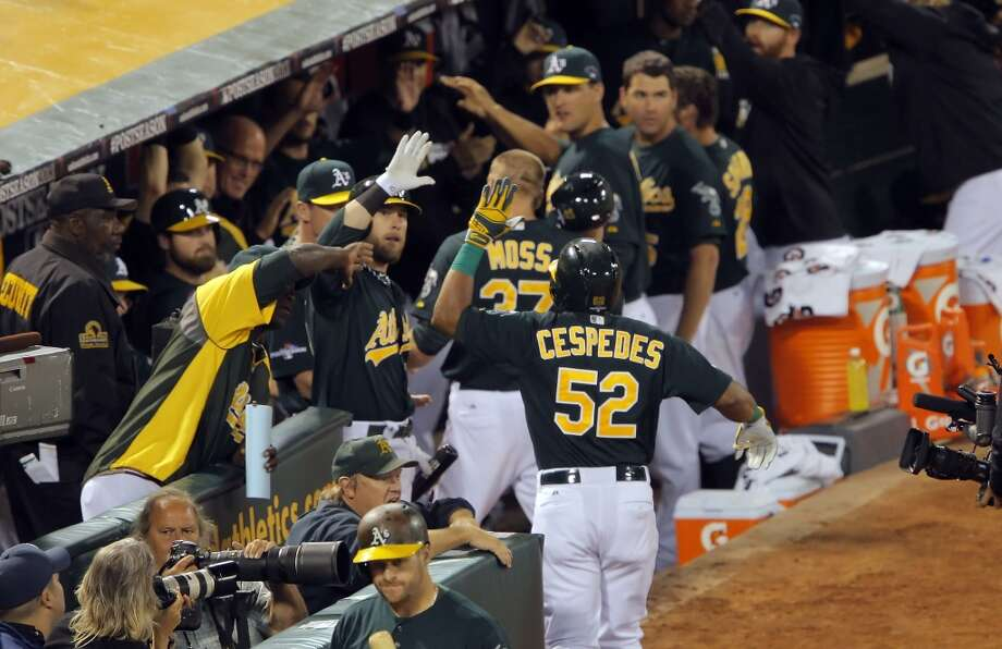 Yoenis Cespedes returns to the dugout after hitting a two-run homerun in the seventh inning. The Oakland Athletics played the Detroit Tigers in Game 1 of the American League Division Series at O.co Coliseum in Oakland, Calif., on Friday, October 4, 2013. Photo: The Chronicle