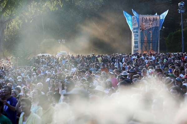 The crowd is seen through exhaled smoke and afternoon light as they watch Bonnie Raitt perform at the Hardly Strictly Bluegrass Festival in Golden Gate Park, in San Francisco, Ca, on Friday Oct. 4, 2013