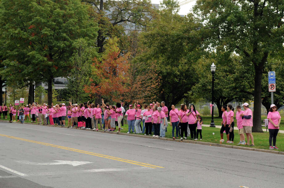"Breast cancer survivors and supporters kick off Stamford Hospital's annual ""Paint the Town Pink"" campaign by donning pink and lining the sidewalk along Mill River Park in Stamford, Conn., October 5, 2013. The campaign, in its ninth year, is aimed at raising awareness and stressing the importance of early detection. Photo: Keelin Daly / Stamford Advocate Freelance"