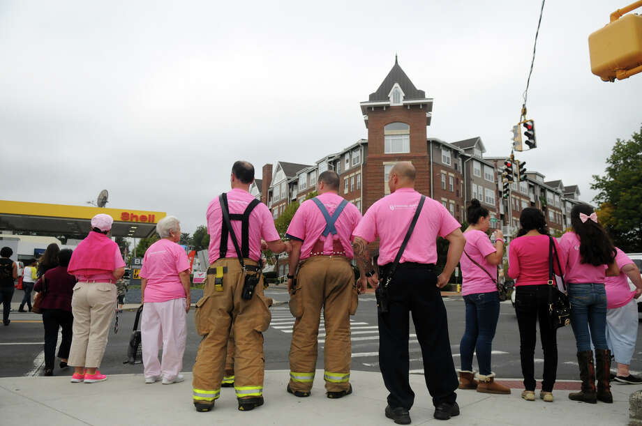 "Stamford Fire and Rescue firefighters join breast cancer survivors and supporters to kick off Stamford Hospital's annual ""Paint the Town Pink"" campaign by donning pink and lining the sidewalk along Mill River Park in Stamford, Conn., October 5, 2013. The campaign, in its ninth year, is aimed at raising awareness and stressing the importance of early detection. Photo: Keelin Daly / Stamford Advocate Freelance"