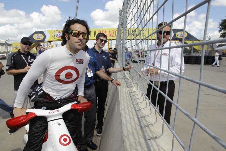 IndyCar driver, Dario Franchitti, left, takes a look at the problem with track as he talks with IndyCar race director Beaux Barfield, right, at turn one of the Grand Prix of Houston course at Reliant Park Friday, Oct. 4, 2013, in Houston. Race practice was delayed while officials installed a temporary chicane to help driver avoid a problem with the surface of the track. IndyCar qualifying was reschedule for Saturday. Officials plan to make repairs to track overnight. ( Melissa Phillip / Houston Chronicle ) Photo: Melissa Phillip, Houston Chronicle