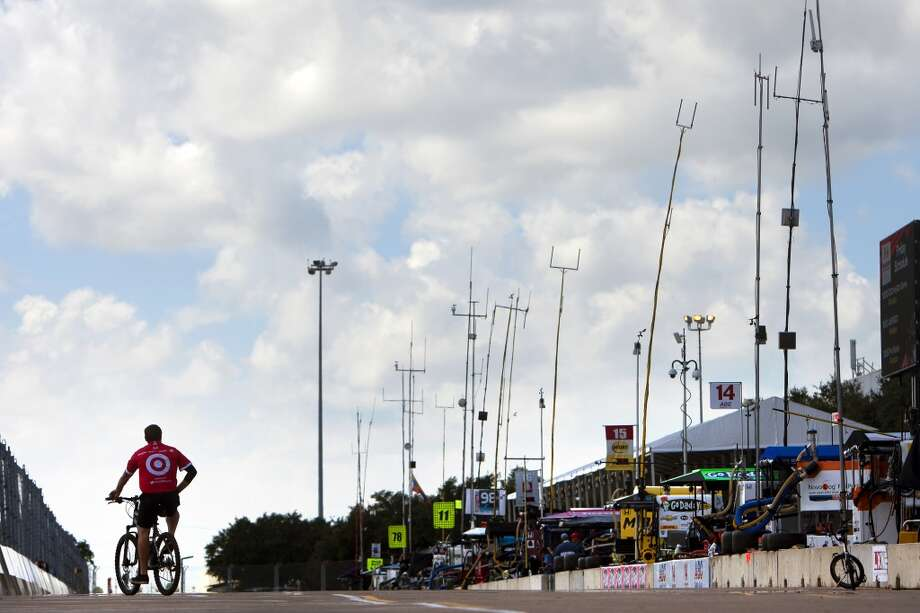 A Target pit crew member rides a bicycle down pit lane at the Grand Prix Houston, Friday, Oct. 4, 2013, in Houston. (Cody Duty / Houston Chronicle) Photo: Cody Duty, Houston Chronicle
