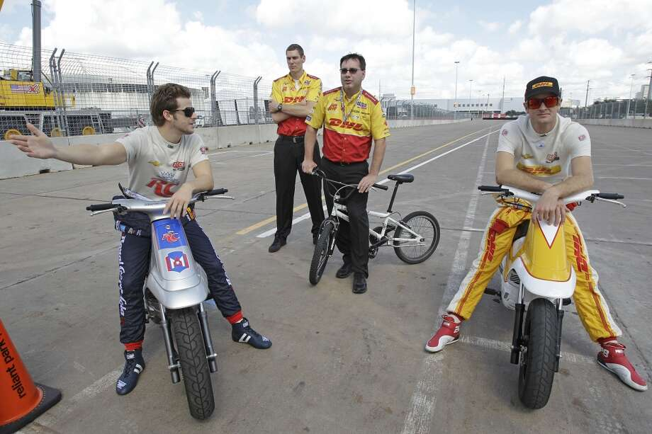 IndyCar drivers, Marco Andretti, left, and Ryan Hunter-Reay, right, sit along track after race practice was delayed due to a problem with the track surface at turn one of the Grand Prix of Houston course at Reliant Park Friday, Oct. 4, 2013, in Houston. Shown in center background are Andretti Autosports crew members Andy Listes, center left, and Ray Gosselin, center right. Practice was delayed while officials installed a temporary chicane to help driver avoid a problem with the surface of the track. IndyCar qualifying was reschedule for Saturday. Officials plan to make repairs to track overnight. ( Melissa Phillip / Houston Chronicle ) Photo: Melissa Phillip, Houston Chronicle