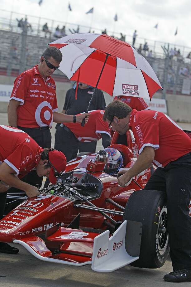 IndyCar driver, Scott Dixon, is shaded with an umbrella while in pits during practice at Grand Prix of Houston course at Reliant Park Friday, Oct. 4, 2013, in Houston. Race practice was delayed while officials installed a temporary chicane to help driver avoid a problem with the surface of the track. IndyCar qualifying was reschedule for Saturday. Officials plan to make repairs to track overnight. ( Melissa Phillip / Houston Chronicle ) Photo: Melissa Phillip, Houston Chronicle