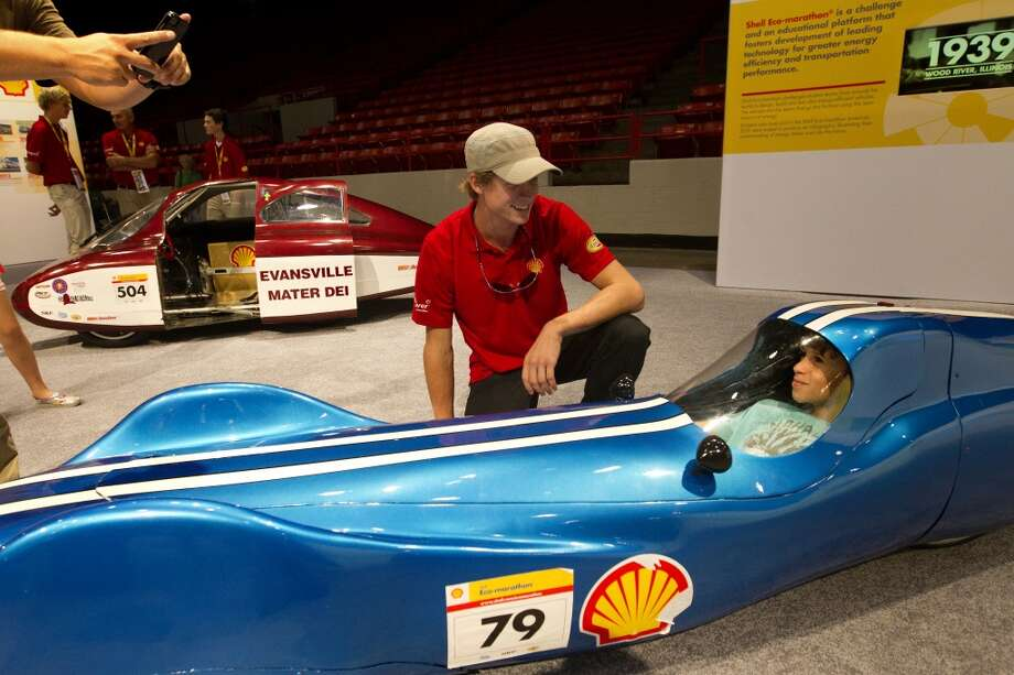 Daniel Cardozo, 9, right, smiles as he sits in a concept car at the Grand Prix Houston, Friday, Oct. 4, 2013, in Houston. The car is all carbon fiber, weighs about 150 pounds and is rear-wheel drive. (Cody Duty / Houston Chronicle) Photo: Cody Duty, Houston Chronicle