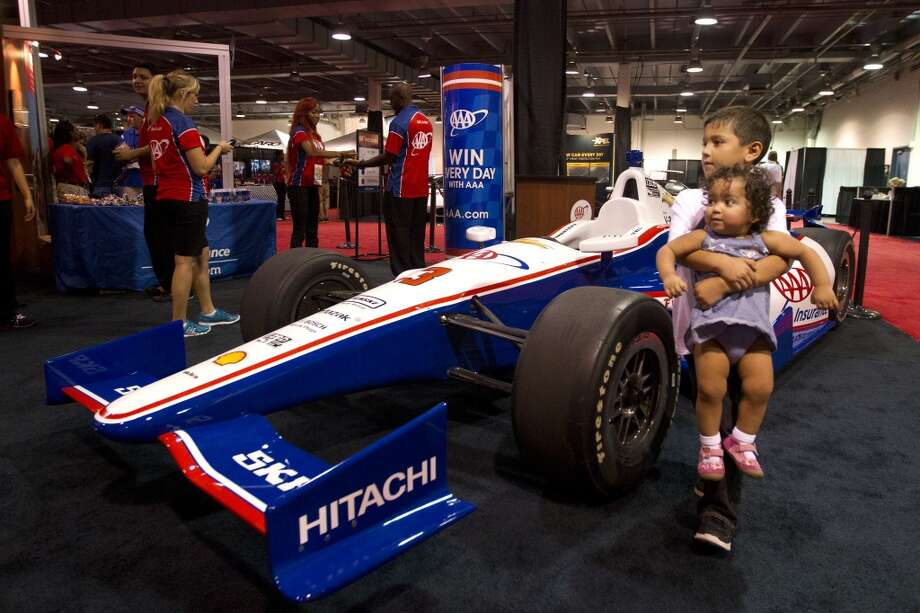 Hector PeÒa, 8, carries his 18-month-old sister Olivia PeÒa as they look at an Indy car at the Grand Prix Houston, Friday, Oct. 4, 2013, in Houston. (Cody Duty / Houston Chronicle) Photo: Cody Duty, Houston Chronicle
