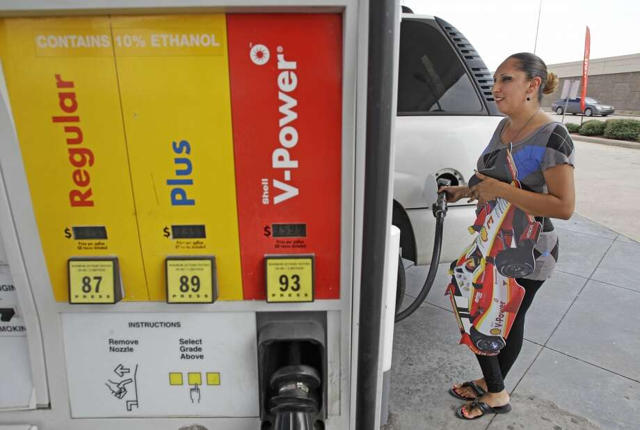 Customer Claudia Najera of Houston finishes pumping at the Shell Station, 1620 S Loop W., after she meet IndyCar driver Helio Castroneves pumps gas and received a free tank of gas and Grand Prix of Houston tickets in a promotion Thursday, Oct. 3, 2013, in Houston.  Helio surprised customers and gave them a free tank of gas and the choice of prizes that included a ride in a two-seater IndyCar, $2,500 worth of Shell V-Power Gasoline, and tickets to the Shell-Pennzoil Grand Prix of Houston. The first customer took the first place prize of $2,500 worth of gas.  ( Melissa Phillip / Houston Chronicle ) Photo: Melissa Phillip, Houston Chronicle