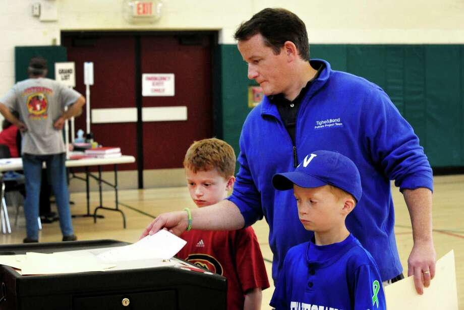 Newtown residents vote on a referendum accepting $49.25 million from the state to demolish the current Sandy Hook Elementry School and build a new one. David Connors is seen voting here with his sons Michael, left, and Will, both 9, at Newtown Middle School in Conn. Saturday, Oct. 5, 2013. Photo: Michael Duffy / The News-Times