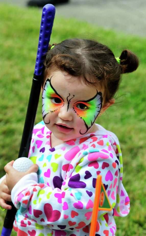 Jasmyn Ramriez, 2, plays miniture golf during the United Methodist Church's Pumpkin Festival in Danbury, Conn. Saturday, Oct. 5, 2013. Photo: Michael Duffy / The News-Times