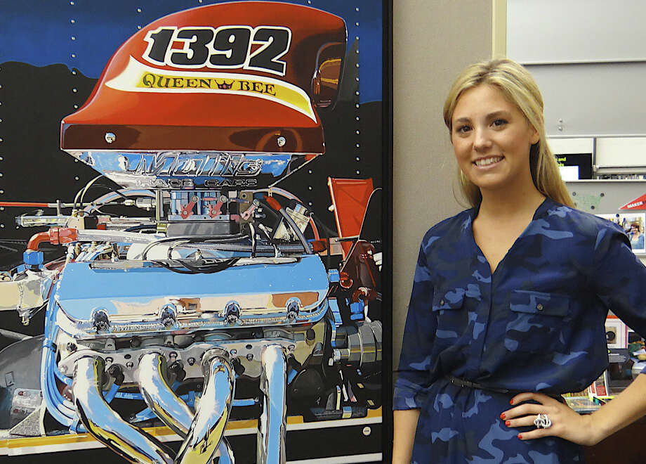 "Drag racer Sarah Edwards, 21, beside ""Queen Bee,"" a depiction of her car painted by Ken Scaglia, in a new exhibit at Westport Library. Photo: Mike Lauterborn / Westport News contributed"